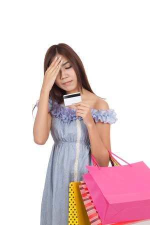 Asian woman headache wtih credit card  and shopping bags  isolated on white background photo