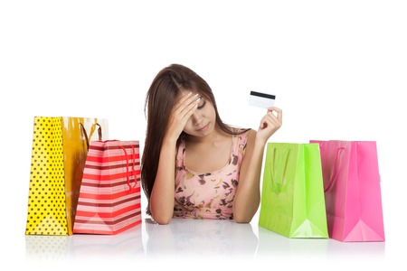 Beautiful Asian woman fed up with a credit card and shopping bags on table  isolated on white background 스톡 콘텐츠