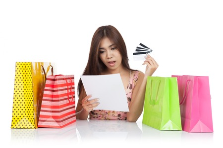 Beautiful Asian woman shock with a credit card statement and shopping bags  isolated on white background photo
