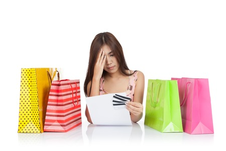 financial report: Beautiful Asian woman headache with credit card statement and shopping bags  isolated on white background Stock Photo