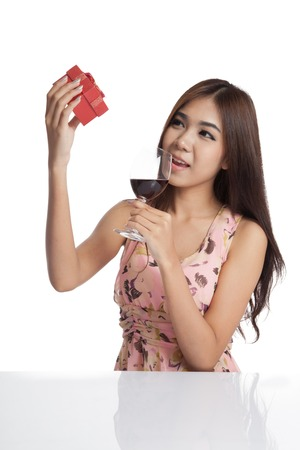 Beautiful Asian woman with gift box and red wine  isolated on white  photo