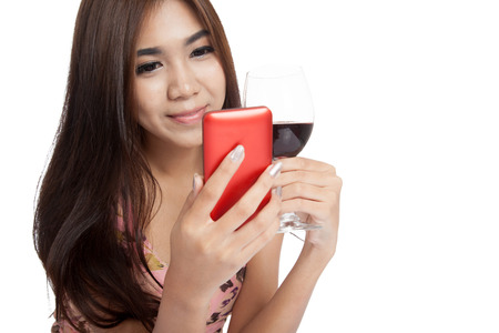 Beautiful Asian woman smile with mobile phone and red wine  isolated on white  photo