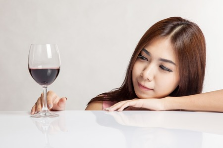 Beautiful Asian woman happy looking at red wine on white table on gray  photo