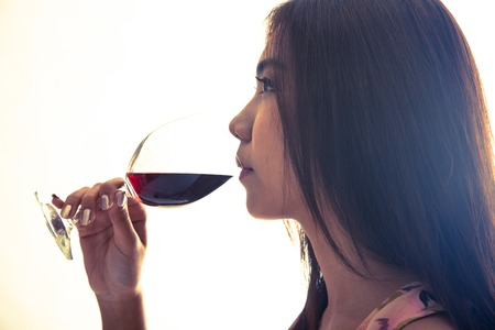 Beautiful Asian woman drink red wine with flare photo