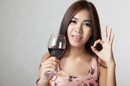 Beautiful Asian woman show OK sign hold glass of  red wine on gray  photo