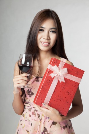 Beautiful Asian woman with red wine and gift box on gray  photo