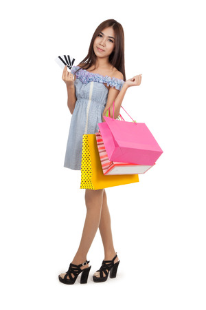 Beautiful Asian woman walking with shopping bags show credit cards   isolated on white  photo