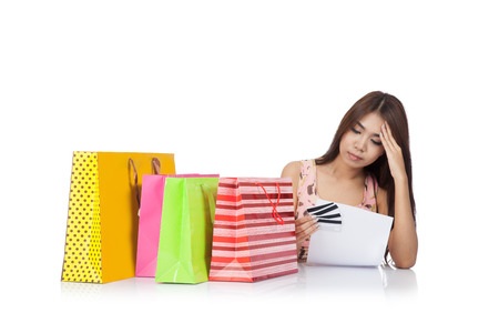 Beautiful Asian woman headache with a credit card statement and shopping bags  isolated on white  photo