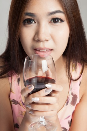 Close up of  beautiful Asian woman hold glass of  red wine on gray  photo