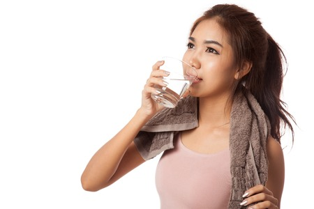 Tired workout asian woman drinking water  isolated on white  photo