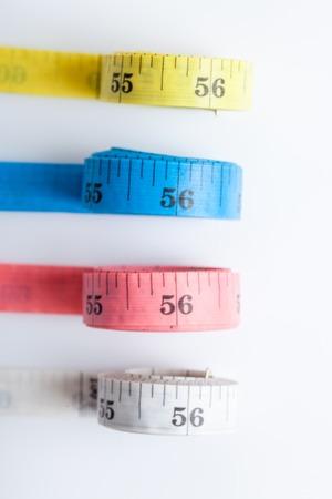 白い背景の上の 4 つのカラフルな測定テープのクローズ アップ 写真素材