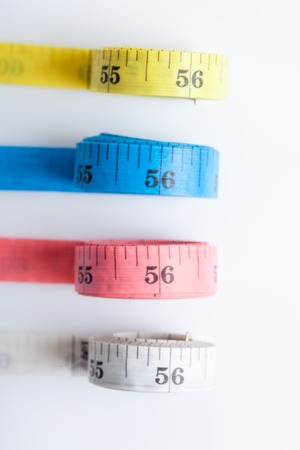 Close up of four colorful measuring tapes on white background