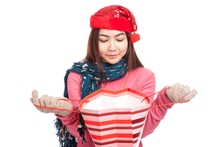 holiday spending: Asian girl with red christmas hat smile open shopping bag  isolated on white background Stock Photo