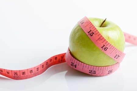Measuring tape with green apple on white background photo