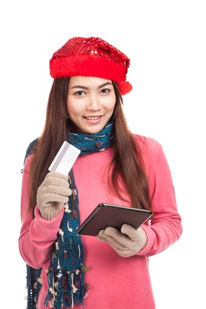 Asian girl with red christmas hat,credit card and tablet PC  isolated on white background photo