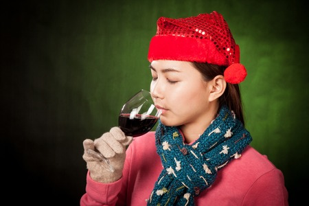 Asian girl with red christmas hat drink red wine on dark green  photo