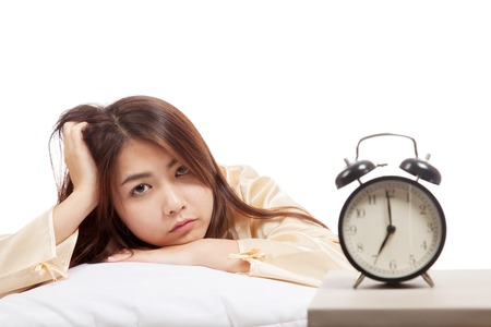 Sleepy Asian girl  wake up  with pillow and alarm clock  isolated on white background photo