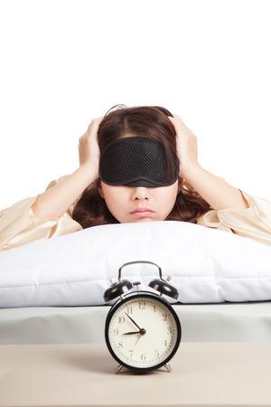 Sleepy Asian girl with eye mask and alarm clock  isolated on white background photo