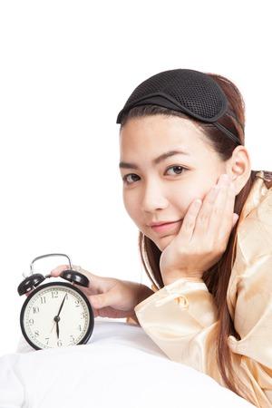 Happy Asian girl wake up with eye mask  and alarm clock  isolated on white background photo