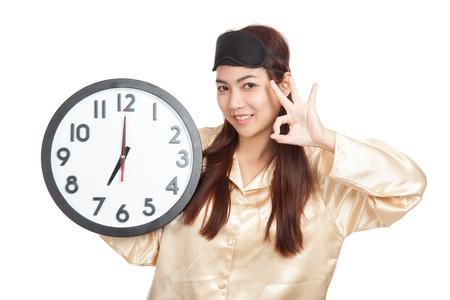 Happy Asian girl with eye mask and clock show OK sign  isolated on white background photo