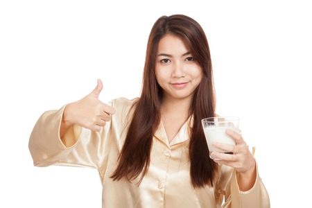 Happy Asian woman in pajamas show thumbs up with  milk  isolated on white background photo
