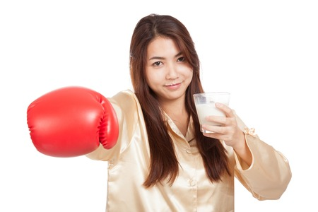 Healthy Asian woman with boxing glove and glass of milk  isolated on white background photo