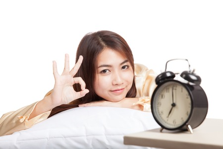Happy Asian girl  wake up show OK with alarm clock  isolated on white background