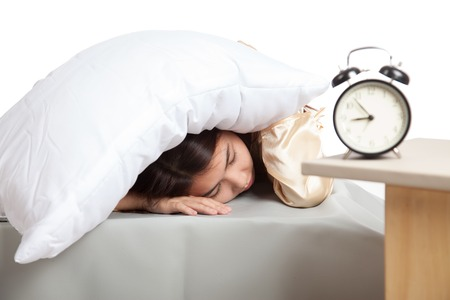 Sleepy Asian girl use pillow cover ears and alarm clock  isolated on white background