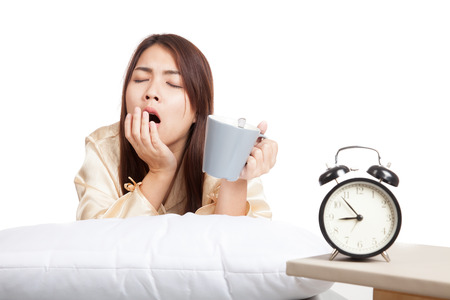 Asian girl  wake up , yawn with alarm clock and  coffee cup  isolated on white background