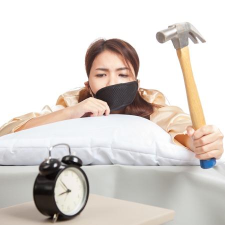 Sleepy Asian girl wake up hit alarm clock with hammer  isolated on white background Foto de archivo