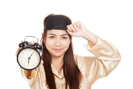 Happy Asian girl with eye mask  show alarm clock  isolated on white background photo