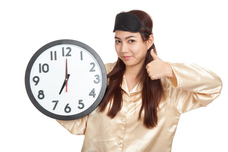 Happy Asian girl with eye mask and clock show thumbs up  isolated on white background photo