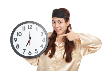 Happy Asian girl with eye mask point to a clock  isolated on white background photo