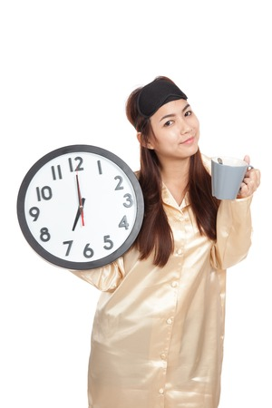 looking good: Happy Asian girl with eye mask,coffee cup and clock  isolated on white background