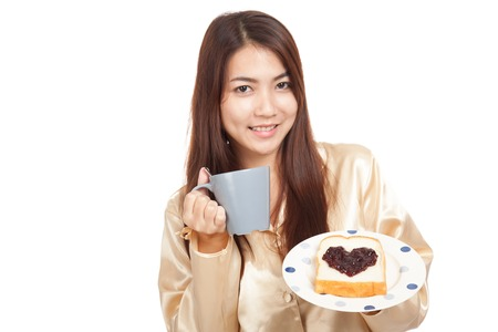 looking good: Asian woman in pajamas with coffee and heart shape jam on bread  isolated on white background