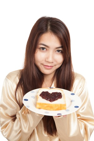 Asian woman in pajamas with bread and heart shape berry jam  isolated on white background photo