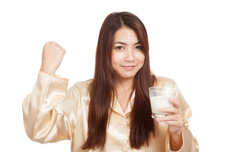 Healthy Asian woman in pajamas fist up with glass of milk  isolated on white background photo