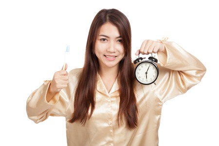 Asian woman in pajamas with toothbrush and clock  isolated on white background