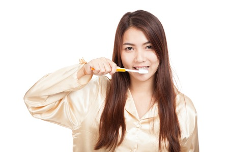 Asian woman in pajamas with toothbrush  isolated on white background Stock Photo