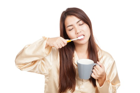 Asian woman in pajamas clean her tooth with toothbrush  isolated on white background 스톡 콘텐츠
