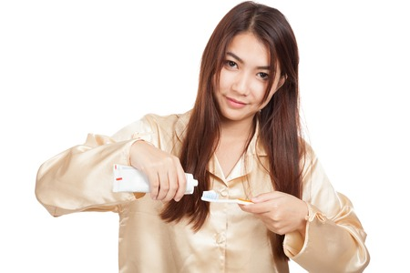 Asian woman in pajamas smile with toothbrush and toothpaste  isolated on white background photo