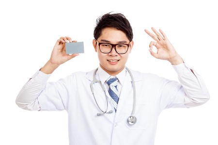 Asian male doctor show a card and OK sign  isolated on white background photo