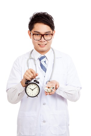 Asian male doctor show a clock and pills  isolated on white background photo