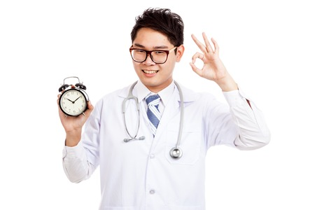 Asian male doctor show OK with a clock  isolated on white background photo