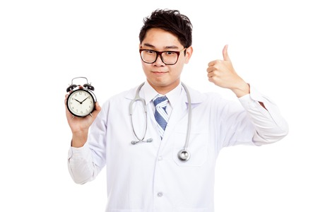 Asian male doctor show thumbs up with a clock  isolated on white background photo