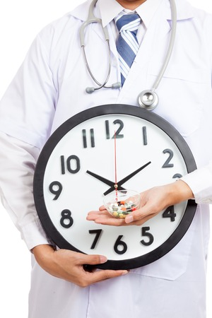 Close up of Asian male doctor show a clock and pills photo