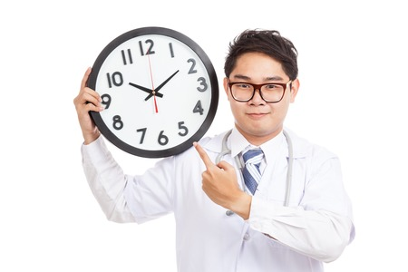 Asian male doctor point to a clock  isolated on white background