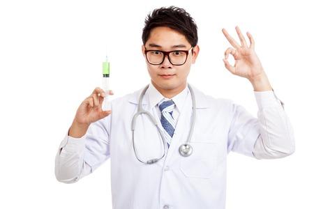 Asian male doctor hold syringe show OK sign  isolated on white background photo