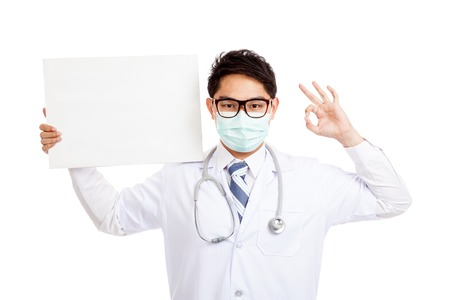 Asian male doctor wear mask show OK with blank banner  isolated on white background photo