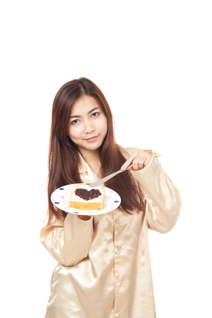 Asian woman in pajamas with bread and heart shape jam  isolated on white background photo